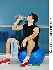 Muž pije vodu ve fitku