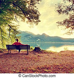 Muž sedí na dřevěné lavici u jezera. Banka pod stromem