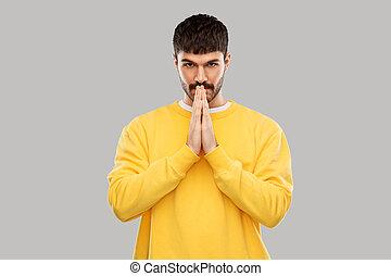 Muž ve žlutém mikině, modlení nebo díky