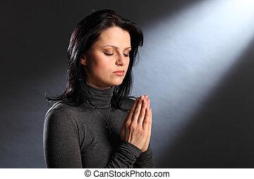 Náboženské oči zavírají mladou ženu v modlitbě