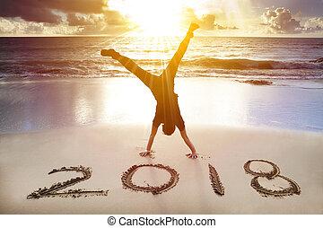 Na pláži se drží chlap. Šťastný nový rok 2018