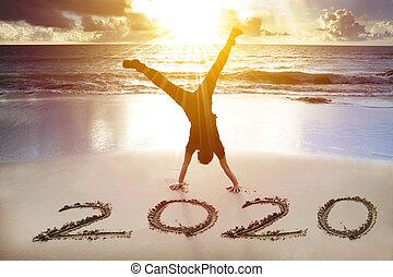 Na pláži se drží chlap. Šťastný nový rok 2020