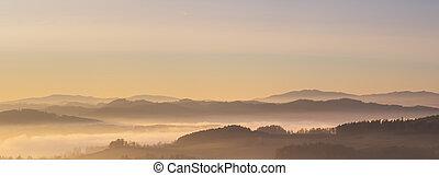 Nešťastná krajina v západu slunce, hory stoupají z oblaků mlhy, z nebe