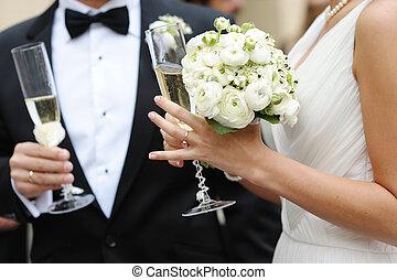 Nevěsta a ženich drží šampaňské