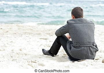 Obchodník, který sedí na pláži sám a užívá si výhled