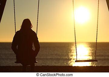 Osamělá žena se dívá na západ slunce sama v zimě