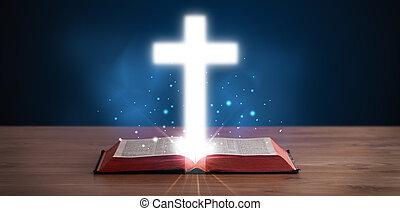 Otevřená Bible s rozsvěceným křížem uprostřed