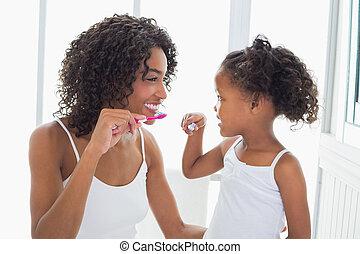 Pěkná matka s dcerou, co si čistí zuby