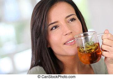 Přístav mladé ženy, která pije bylinkové infuze