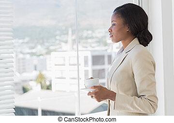 Pohled na elegantní mladou podnikatelku s čajem v kanceláři
