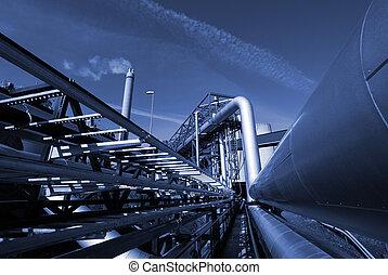 Průmyslové ropovody na trubkovém mostě proti obloze v modrém tónu
