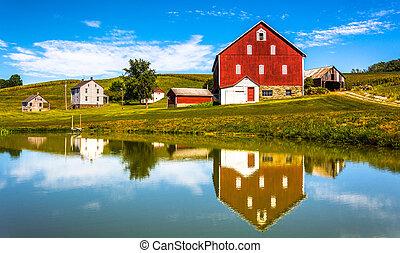 Reflekce domu a stodola v malém jezírku, ve venkovském okrese, Pensylvanie.