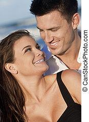 Romantický muž a žena se šťastně smáli na pláži
