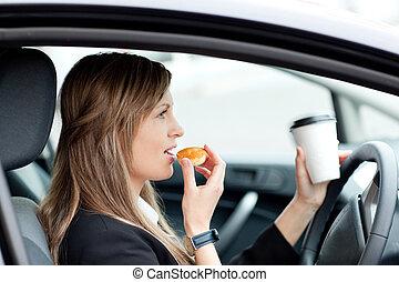 Roztomilá podnikatelka, co jí a pije, zatímco jezdí do práce
