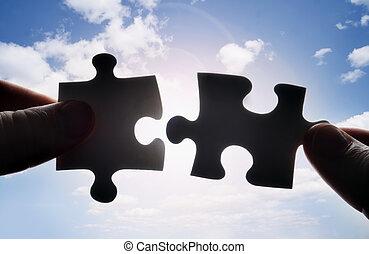 Ruce se snaží dát dohromady dvě skládačky