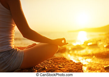 Ruka ženy meditující v józe na pláži