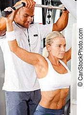 Schopná žena a osobní trenérka v tělocvičně