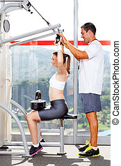 Schopná žena v tělocvičně s osobním trenérem