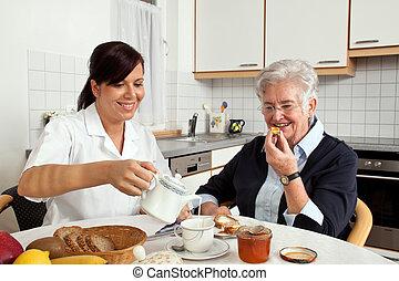 Sestra pomáhá starším ženám na snídani