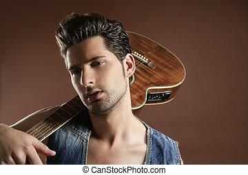 Sexy mladý mužský kytarista na hnědém