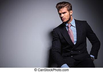 Sezatý mladý model v obleku se dívá jinam