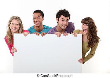 Skupina přátel drží prázdný plakát