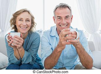 Smívající se ve středním věku, sedící na gauči a dává si kafe