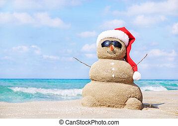 Smívalířící sněhulák v červeném klobouku na pláži.