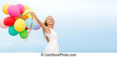 Smívala žena s barevnými balónky venku