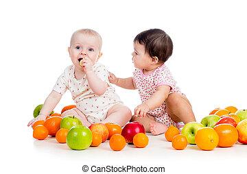 Směšné děti, které jedí zdravé ovoce, izolované na bílém pozadí