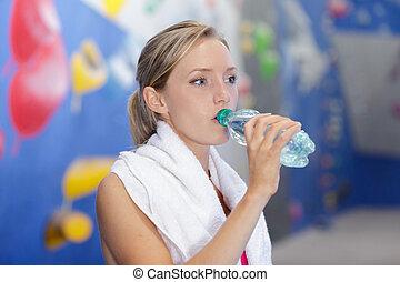 Sportovní mladá žena pije vodu v tělocvičně