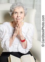 Stará žena s biblí a růženec se modlí