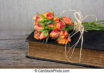 Stará bible s oranžovou kytkou