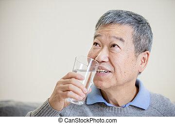 Starý asijský muž pije vodu