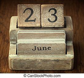 Starý dřevěný kalendář, který ukazuje datum 23. června