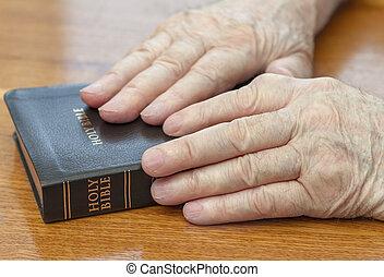 Starý muž si dává na Bibli