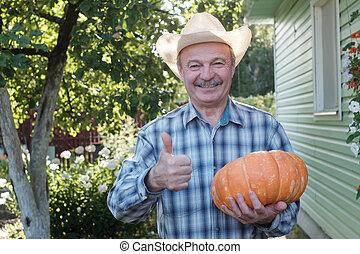 Starší šťastný hispánec drží dýň v ruce.