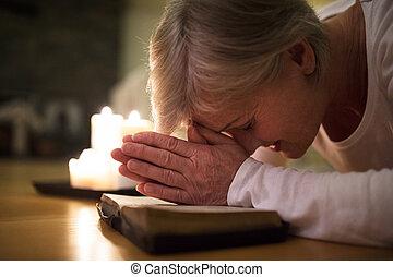 Starší žena se modlila, ruce svázaly na její bibli.