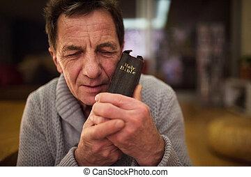 Starší muž, který se modlí, drží v rukách bibli, zavřené oči.