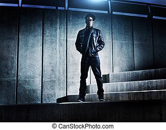 Super africký americký muž na netopýřích betonových schodech