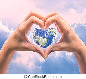 Svět ve tvaru srdce, s lidskými rukami, s rozmazanými přírodními kořeny. Světový den, který byl vytvořen nasy
