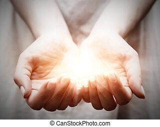 Světlo v rukou mladých žen. Sdílení, darování, ochrana