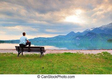 Unavený dospělý muž v modrém tričku sedí na staré dřevěné lavici u jezera