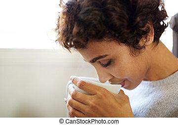 Uzavřená mladá africká americká žena pije čaj ze šálku