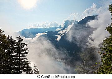 View z hor, les a modré nebe s mraky ve vesnici a jezírku