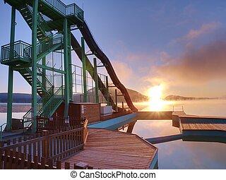 Vysoká ocelová věž s klouzající po pláži. Studené podzimní ráno s mlhou
