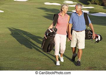 Vysokoškolský pár chodících po golfu s taškami