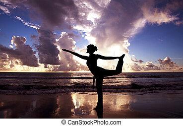 Yogská žena na krásné pláži za úsvitu