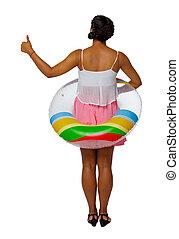 Zadní pohled na africkou americkou ženu na pláži, kde se objeví nafukovací kruh.