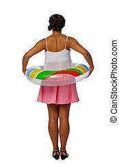 Zadní pohled na africkou americkou ženu na pláži s nafukovacím kruhem.